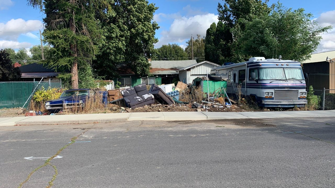 Homeowners say City of Spokane won't do anything about trash build-up in neighbor's yard