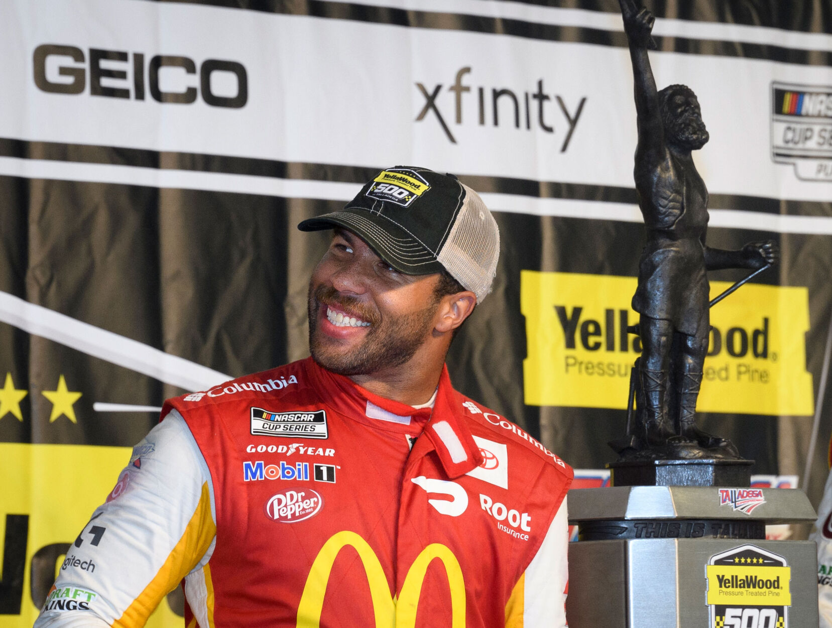 <p>Bubba Wallace celebrates next to the trophy after winning a NASCAR Cup series auto race Monday in Talladega, Ala. The race was stopped mid-race due to rain.</p>